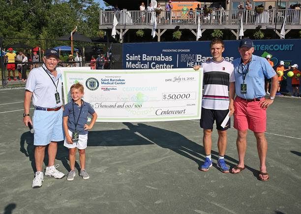 Pictured left to right: Bruce Schonbraun, Chairman, Saint Barnabas Medical Center Trustees; Sam Schonbraun, Bruce's grandson; Stefan Kozlov, match winner; and Clay Bibbee, Managing Partner, Centercourt Athletic Club.